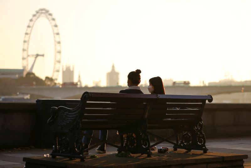 People wearing protective face masks sit on a bench on Embankment during sunset, amid the coronavirus disease (COVID-19) outbreak, in London