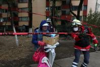 Members of Civil Protection accompany a resident after recovering belongings from an apartment building damaged by an earthquake that struck southern Mexico, in Mexico City