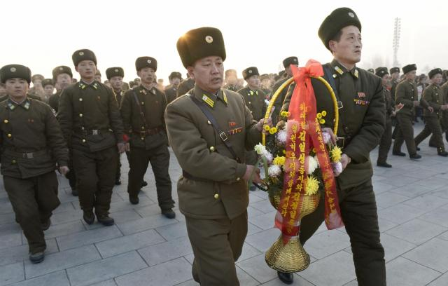 North Korean soldiers offer flowers to bronze statues of North Korea's late founder Kim Il Sung and late leader Kim Jong Il at Mansudae in Pyongyang