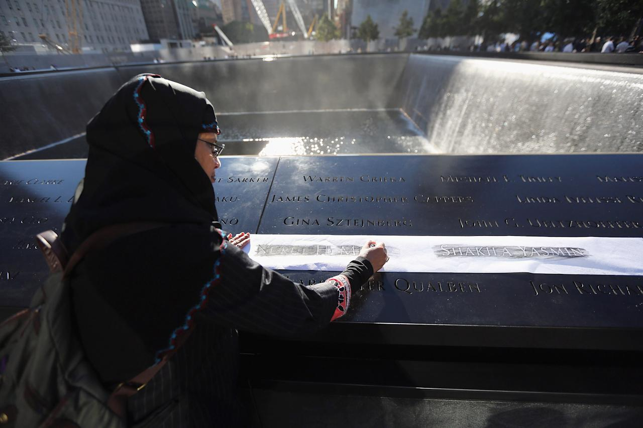 NEW YORK - SEPTEMBER 11:  Khudeza Begum etches the name of her slain nephew during ceremonies for the eleventh anniversary of the terrorist attacks on lower Manhattan at the World Trade Center on September 11, 2012 in New York City. New York City and the nation are commemorating the eleventh anniversary of the September 11, 2001 attacks which resulted in the deaths of nearly 3,000 people after two hijacked planes crashed into the World Trade Center, one into the Pentagon in Arlington, Virginia and one crash landed in Shanksville, Pennsylvania.  (Photo by John Moore/Getty Images)