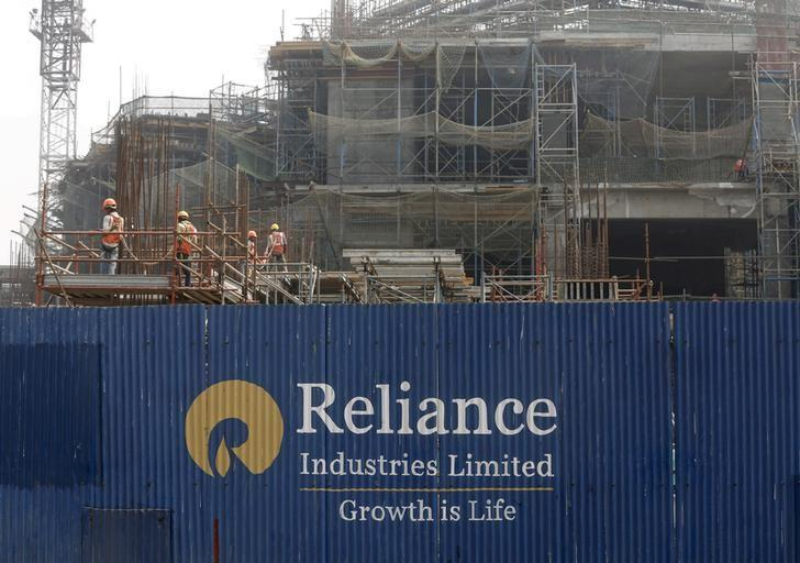 Labourers work behind an advertisement of Reliance Industries Limited at a construction site in Mumbai