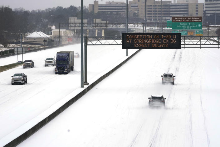 FILE - In this Feb. 15, 2021, file photo, an electronic message board advises drivers of potential congestion as they drive over snow on Interstate 55 in north Jackson, Miss. Efforts to vaccinate Americans against COVID-19 have been stymied by a series of winter storms and outages in parts of the country not used to extreme cold weather, and hobbled transportation hubs and highways. (AP Photo/Rogelio V. Solis, File)