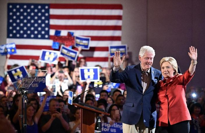 Democratic presidential candidate Hillary Clinton and husband Bill Clinton wave to a cheering crowd after winning the Nevada democratic caucus on February 20, 2016 (AFP Photo/Josh Edelson)