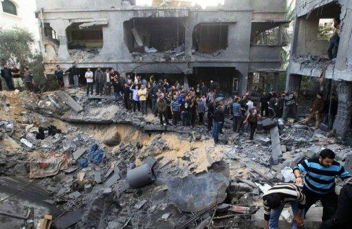 Palestinians gather around the destroyed home of the al-Dallu family following an Israeli air strike in Gaza City, on November 18, 2012. At least seven members of the same family, including four children, were among nine people killed when an Israeli missile struck a family home in Gaza City, the health ministry said