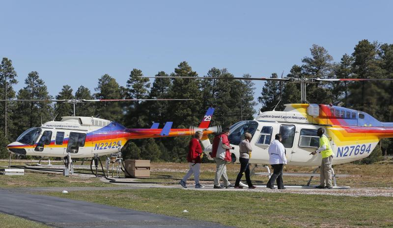 In this Oct. 11, 2013 photo, tourists prepare to get on a helicopter prior to taking a tour of the Grand Canyon, at Grand Canyon National Park Airport in Tusayan, Ariz. Air tour operators that use aircraft with quiet technology will be able to fly more people over the Grand Canyon. The Federal Aviation Administration said it plans to release 1,721 flight allocations this year that had been abandoned to those commercial tour operators, as long as their active fleet doesn't increase noise in the park overall. (AP Photo/Ross D. Franklin)