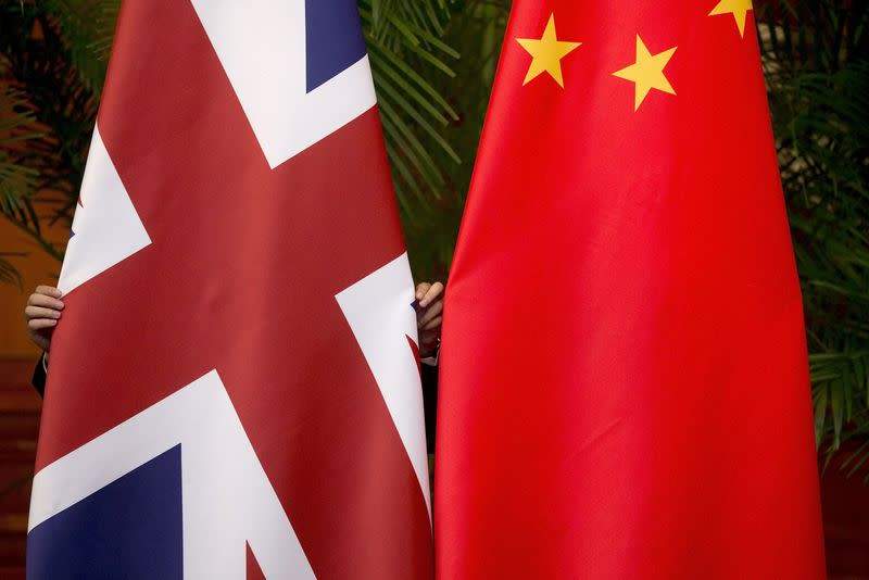 FILE PHOTO: A worker adjusts flags in Beijing