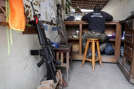A vigilante is pictured the command headquarters in the municipality of Coahuayana