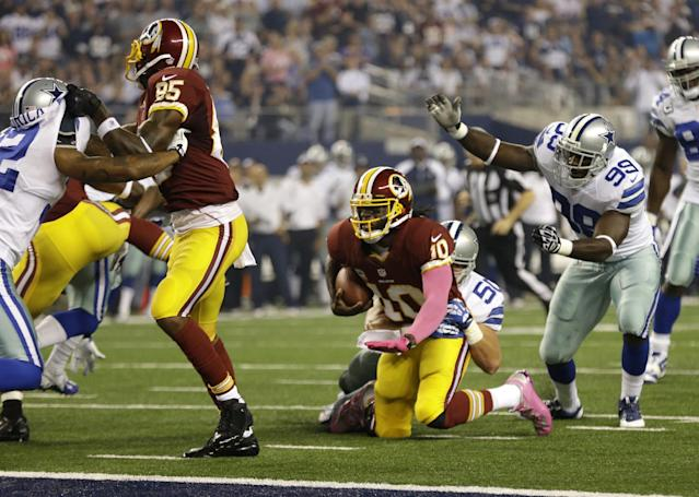 Washington Redskins wide receiver Leonard Hankerson (85) helps against the pressure as quarterback Robert Griffin III (10) is stopped shy of the end zone by Dallas Cowboys middle linebacker Sean Lee (50) in the first half of an NFL football game, Sunday, Oct. 13, 2013, in Arlington, Texas. The Cowboys defensive end George Selvie (99) watches on the play. (AP Photo/LM Otero)
