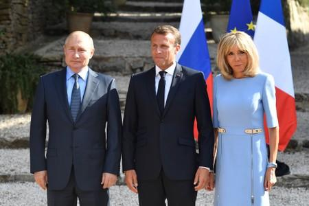 French President Emmanuel Macron and his wife Brigitte Macron pose with Russia's President Vladimir Putin, at the French President's summer retreat of the Bregancon fortress on the Mediterranean coast, near the village of Bormes-les-Mimosas