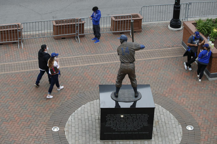 Fans walk by Ernie Banks Statue outside Wrigley Field as a baseball game between the Chicago Cubs and the Los Angels Dodgers was postponed due to the forecast of inclement weather, Monday, May 3, 2021, in Chicago. (AP Photo/Kamil Krzaczynski)