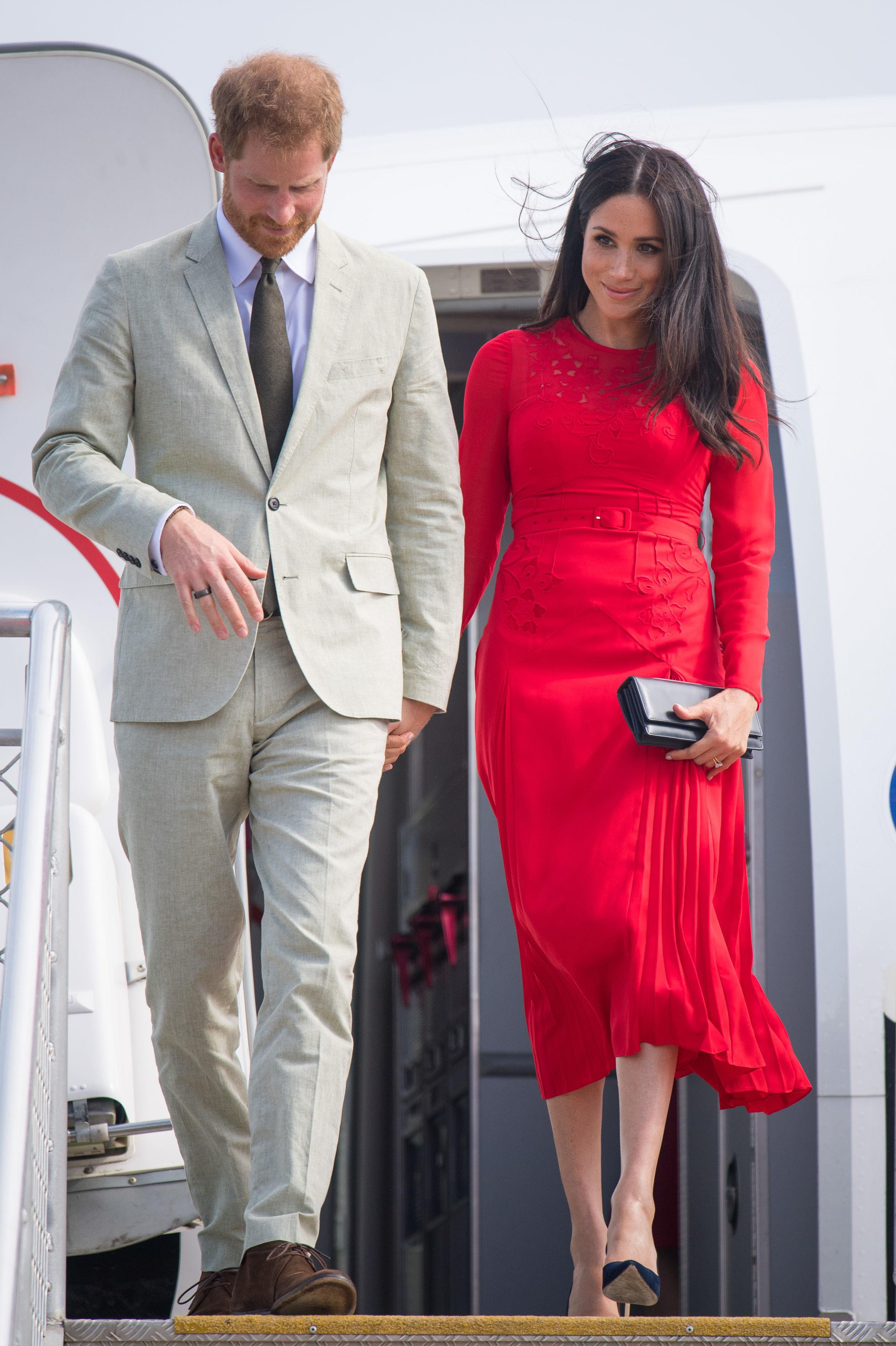 File photo dated 25/10/18 of the Duke and Duchess of Sussex arriving at Fua'amotu Airport, Tonga, with Meghan wearing a £345 red outfit by London fashion brand Self-Portrait.