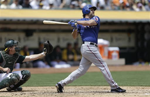 Texas Rangers' Lance Berkman, right, swings for a two-run single off Oakland Athletics' Dan Straily in the third inning of a baseball game Wednesday, May 15, 2013, in Oakland, Calif. (AP Photo/Ben Margot)