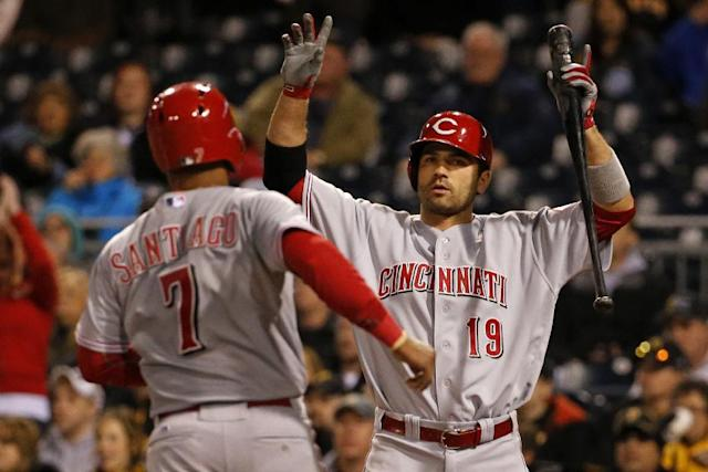 Cincinnati Reds' Ramon Santiago (7) is greeted by Joey Votto (19) as he scores from third on a throwing error by Pittsburgh Pirates catcher Chris Stewart during the fifth inning of a baseball game in Pittsburgh on Wednesday, April 23, 2014. (AP Photo/Gene J. Puskar)