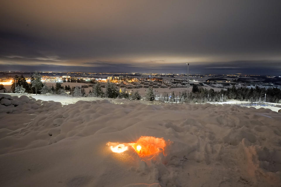 A candle burns on Saturday Jan. 2, 2021, for the victims of the massive landslide that hit the residential area in Ask in Gjerdrum, Norway on Wednesday. The landslide cut across a road through Ask, home to some 5,000 people, leaving a deep, crater-like ravine that cars could not pass. (Haakon Mosvold Larsen/NTB via AP)