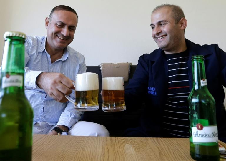 Bassel Abbas (R) of the Arados brewery and friend drink one of the company's locally crafted beers