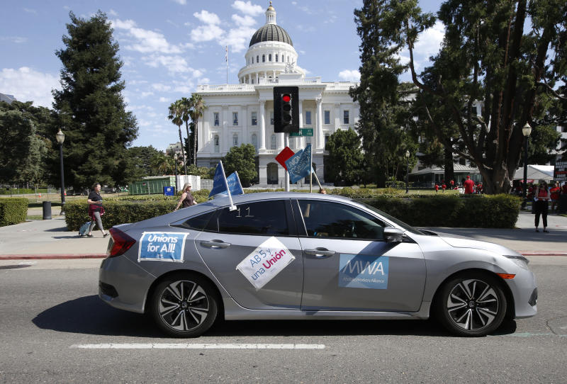 In this Aug. 28, 2019, photo, supporters of a measure to limit when companies can label workers as independent contractors drive their cars past the Capitol during a rally in Sacramento, Calif. California lawmakers are debating a bill that would make companies like Uber and Lyft label their workers as employees, entitling them to minimum wage and benefits. (AP Photo/Rich Pedroncelli, File)