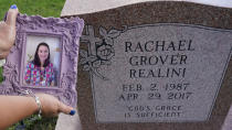 Sharon Grover holds up a photograph of her daughter, Rachael, over the gravesite at Fairview Cemetery, Tuesday, Sept. 28, 2021, in Mesopotamia, Ohio. Grover believes her daughter started using prescription painkillers around 2013 but missed any signs of her addiction as her daughter, the oldest of five children, remained distanced. (AP Photo/Tony Dejak)