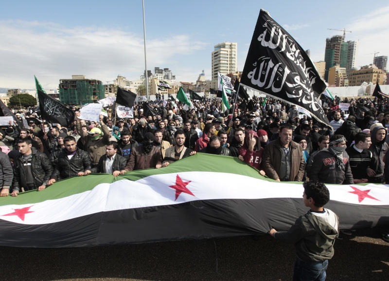 FILE - In this Sunday, March 4, 2012 file photo, Lebanese anti-Syrian regime Salafi protesters carry the Syrian revolutionary flag during a demonstration held by a Salafi group at Martyrs' Square in Beirut, Lebanon. Islamic movements inside and outside Syria are also vying to gain influence through the uprising and their growing power is seeding divisions within an already fractious opposition. The groups run the spectrum from violent, jihadi movements that are not far in ideology to al-Qaida, to hard-line Salafis, to political moderates like the Muslim Brotherhood. (AP Photo/Hussein Malla, File)