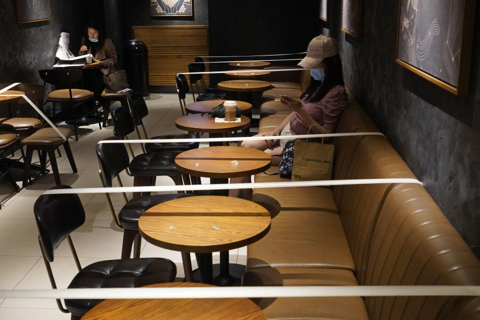 Tables and chairs are taped for the social distancing law enforcement to help curb the spread of the coronavirus at a Starbucks coffee shop in Hong Kong, Monday, March 30, 2020. The new coronavirus causes mild or moderate symptoms for most people, but for some, especially older adults and people with existing health problems, it can cause more severe illness or death. (AP Photo/Vincent Yu)