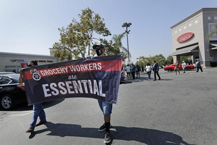 BURBANK, CA - SEPTEMBER 24: Grocery Teamsters Rene Ayala, left, and Jerry Soltero carry a banner during a Teamsters' rally on Thursday, Sept. 24, 2020 in Burbank, CA to call for the protection of grocery workers health package through ongoing contract negotiations with their employers. (Myung J. Chun / Los Angeles Times)