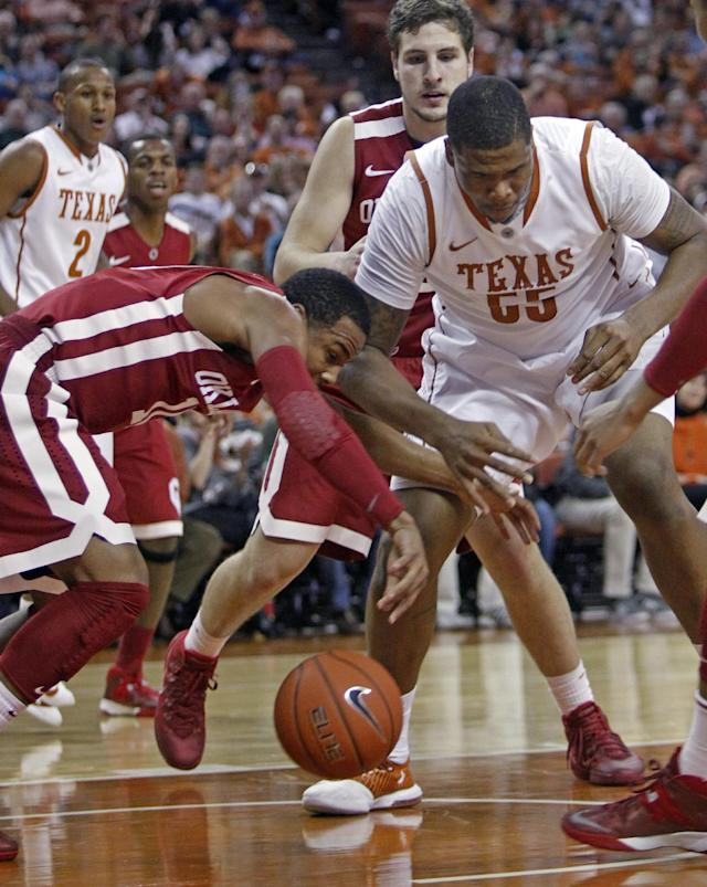 Oklahoma guard Isaiah Cousins (11) scrambles for the loose ball with Texas center Cameron Ridley (55) during the first half of an NCAA college basketball game, Saturday, Jan. 4, 2014, in Austin, Texas. (AP Photo/Michael Thomas)