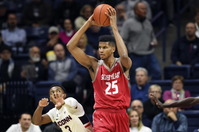 Sacred Heart's Jare'l Spellman (25) controls the ball against Connecticut's Alterique Gilbert (3) in the second half of an NCAA college basketball game, Friday, Nov. 8, 2019, in Storrs, Conn. (AP Photo/Stephen Dunn)