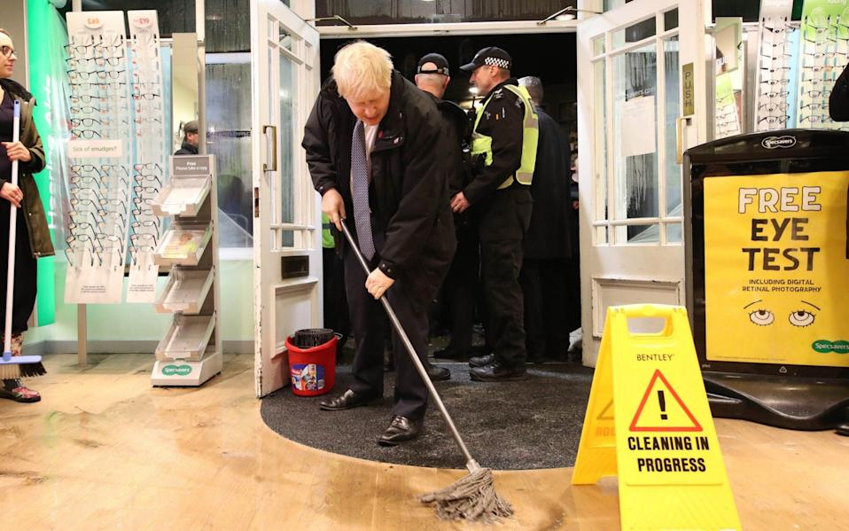 Prime Minister Boris Johnson helps with the clean up at an opticians as he visits Matlock on November 8, 2019 in Sheffield, England. - Getty Images Europe