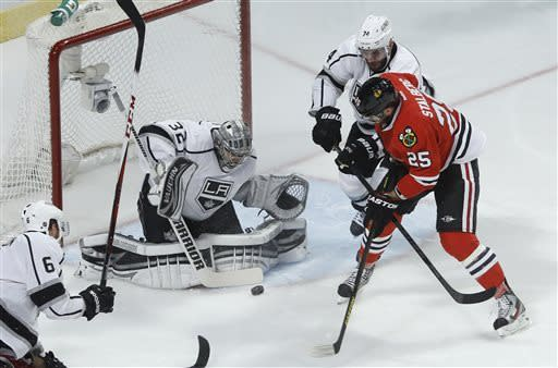 Los Angeles Kings goalie Jonathan Quick (32) blocks a shot attempt by Chicago Blackhawks left wing Viktor Stalberg (25) as Kings center Dwight King (74) helps defend during the first period in Game 1 of the NHL hockey Stanley Cup Western Conference finals Saturday, June 1, 2013, in Chicago. (AP Photo/Charles Rex Arbogast)