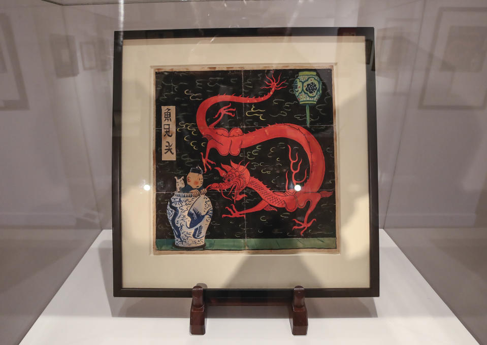 """The inked and water-painted original panel of the comic character Tintin from the 1936 """"The Blue Lotus"""" album drawn by Belgian creator Herge, is displayed at the Artcurial auction house in Paris, Wednesday, Jan. 13, 2021. The art work is estimated to fetch The art work with an estimates value of 2.2 to 2.8 million euros (US $ 2.6 to 3.4 million), is going on sale Thursday. (AP Photo/Michel Euler)"""