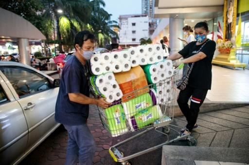 People wearing face masks amid concerns over the COVID-19 coronavirus push a shopping cart full of toilet paper and kitchen rolls at a supermarket in Bangkok on March 16, 2020