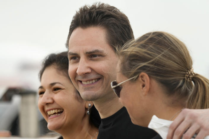 FILE - In this Sept. 25, 2021, file photo, Michael Kovrig, center, embraces his wife Vina Nadjibulla, left, and sister Ariana Botha after arriving at Pearson International Airport in Toronto. Two Canadians, Kovrig and Michael Spavor who were detained in late 2019, days after Huawei's chief financial officer, Meng Wanzhou, was arrested in Canada at the request of U.S. authorities, have been allowed to return to Canada after being released on bail for health reasons, China's Foreign Ministry said Monday, Sept. 27, 2021. (Frank Gunn/The Canadian Press via AP)