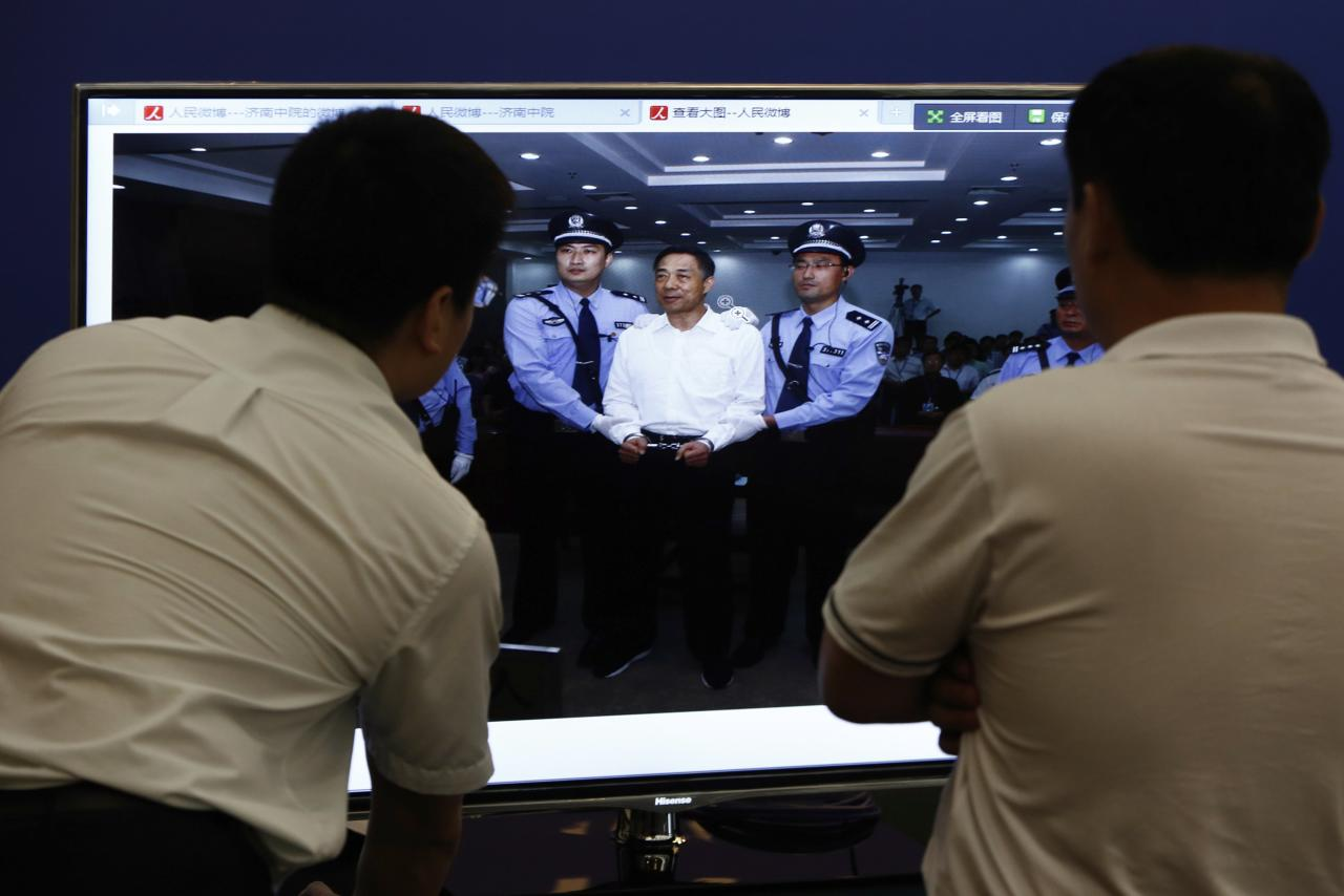 Men look at a screen displaying a picture of disgraced Chinese politician Bo Xilai standing trial on the website of a court's microblog, in Jinan, Shandong province September 22, 2013. The court sentenced former Chongqing Municipality Communist Party Secretary Bo to life in jail on Sunday after finding him guilty on all counts following his dramatic five-day trial last month on charges of corruption, taking bribes and abuse of power.REUTERS/Aly Song (CHINA - Tags: POLITICS CRIME LAW)