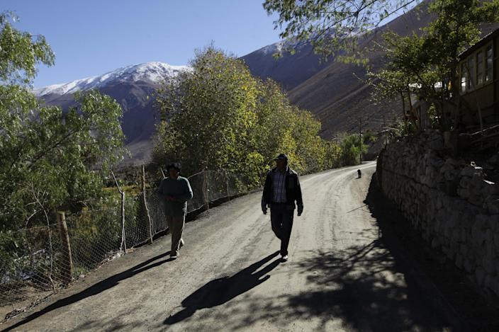 In this May 23, 2013 photo, two men walk along a road in El Corral, a small town of about 200 inhabitants, mostly from the Diaguita ethnic group, near the facilities of Barrick Gold Corp's Pascua-Lama project in northern Chile. The Diaguitas live in the foothills of the Andes, where for as long as anyone can remember they've drunk straight from the glacier-fed river that irrigates their orchards and vineyards with clean water. But since Pascua-Lama gold mine project moved in, the Diaguitas claim the river levels have dropped and some complain of cancerous growths and aching stomachs. (AP Photo/Jorge Saenz)