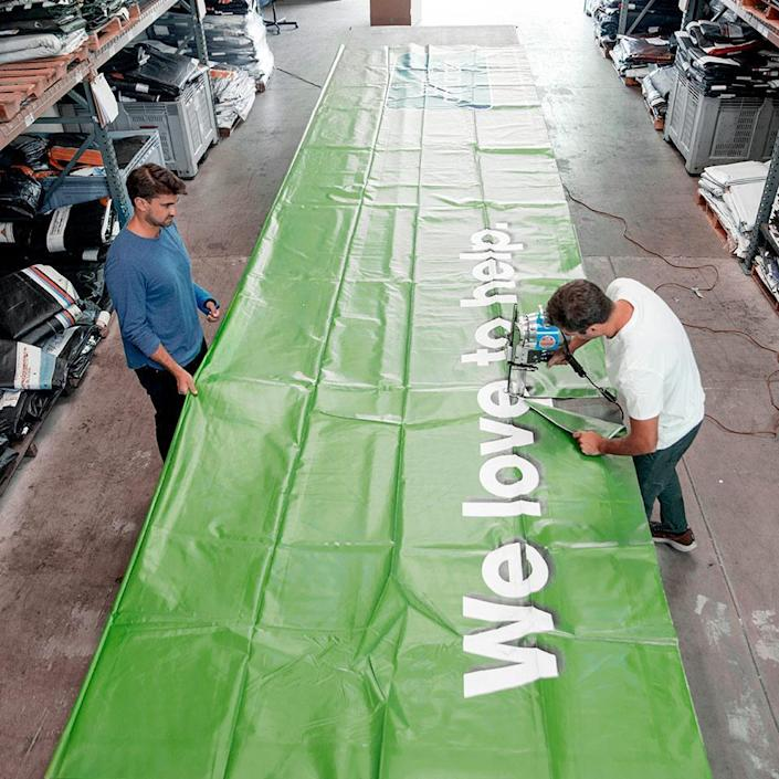 The Rareform team works hard to take apart, wash, and sort all the discarded billboard material they receive.