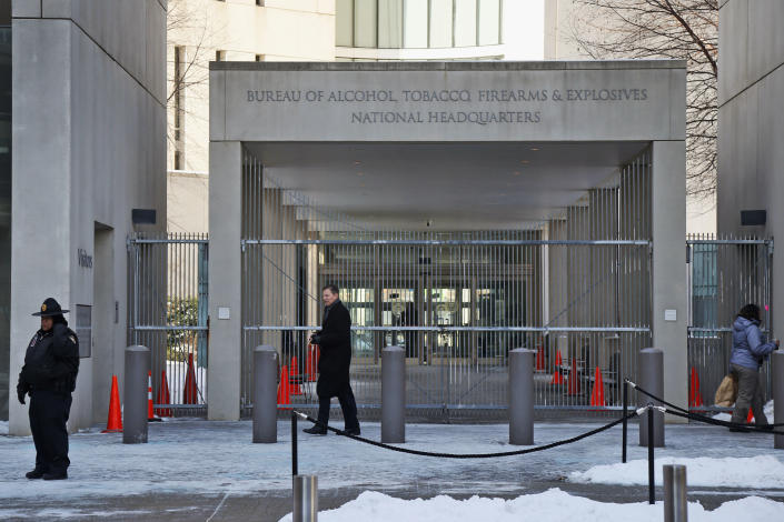 In this Thursday, Jan. 23, 2014 photo, a security official walks in front of the entrance to the national headquarters of the Bureau of Alcohol, Tobacco, Firearms and Explosives in Washington. Illinois' two U.S. senators have proposed renaming the building after prohibition-era crime fighter Eliot Ness, but it won't happen if Ed Burke, the dean of the Chicago City Council and others have their way. Portrayed over the years by Kevin Costner and Robert Stack as an incorruptible hero, Ness' legend is now at risk, with some claiming his role in taking out Chicago mobster Al Capone is as mythical as Mrs. O'Leary's cow starting the Great Chicago Fire. (AP Photo/Charles Dharapak)