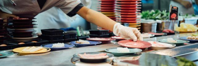 A chef putting a place down on conveyor belt sushi