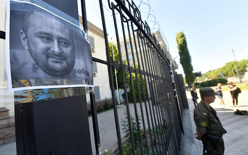 Activists have posted portraits of Arkady Babchenko posted on the gates of the Russian embassy in Kiev - AFP