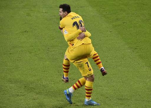 Barcelona's Lionel Messi, celebrates after scoring his team's third goal, with his teammate Antoine Griezmann, during the Spanish La Liga soccer match between Athletic Bilbao and Barcelona at San Mames stadium in Bilbao, Spain, Wednesday, Jan. 6, 2021.(AP Photo/Alvaro Barrientos)