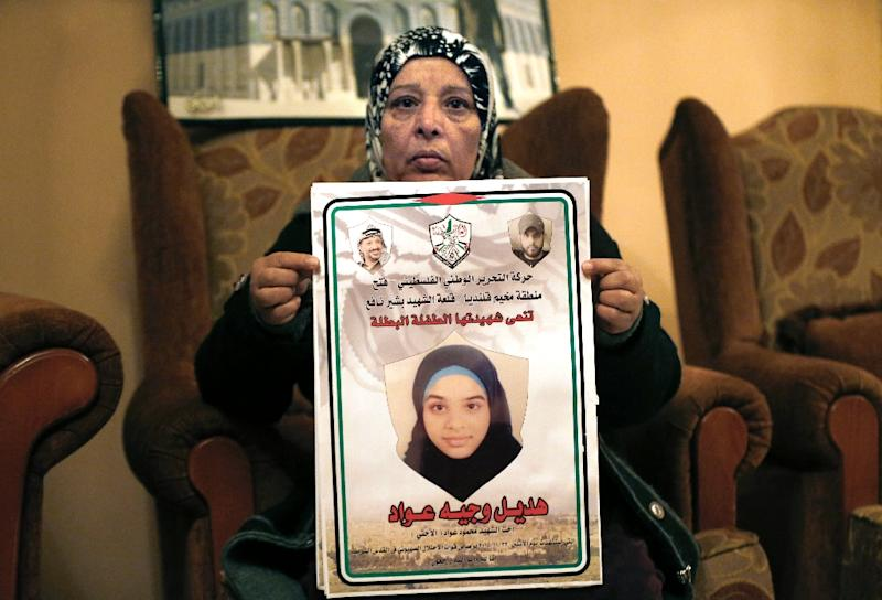Maleeha Awwad poses with a martyr poster showing her son Mahmud and daughter Hadeel, 14 years old, at the family home in the West Bank city of Qalandia near Ramallah, on December 16, 2015 (AFP Photo/Ahmad Gharabli)