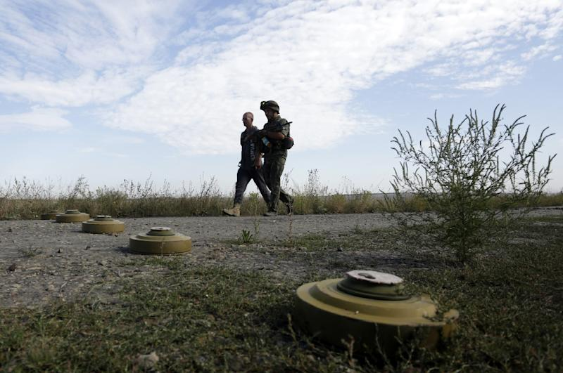 Servicemen walk past anti-tank mines set on the position of Ukrainian forces in the Lugansk region on August 27, 2015 (AFP Photo/Anatolii Stepanov)