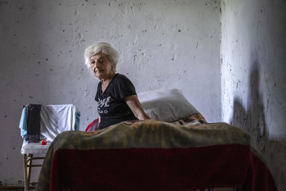 """Anahit Aleqyan sits on a bed in the empty room of her new house in Shurnukh village, about 200 km. (125 miles) south east of Yerevan, Armenia, Tuesday, June 15, 2021. Anahit Aleqyan, a 65-year-old from the village of Shurnkh in southern Armenia, says that her village was cut in two by a newly defined border with Azerbaijan, and she lost her house in the peace deal. """"Every day I come here to gather thyme, look at (my house) and cry,"""" she lamented. (AP Photo/Areg Balayan)"""