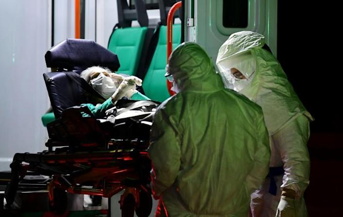 An elderly patient suspected of being infected with the coronavirus is transferred from a nursing home to an ambulance in Belgrano neighbourhood, Buenos Aires (AFP Photo/RONALDO SCHEMIDT)