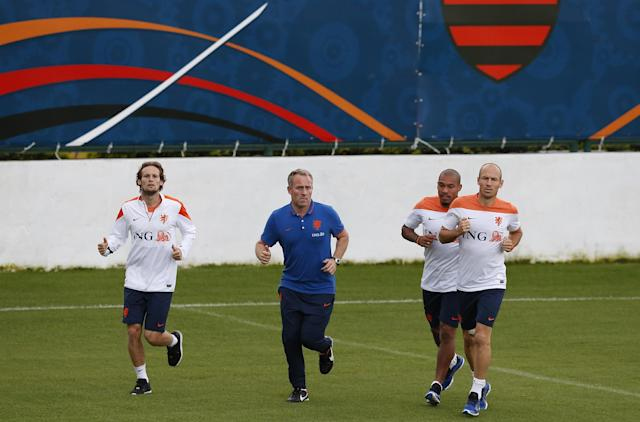 Soccer players Daley Blind, left, Nigel de Jong, second right, and Arjen Robben, right, of the Netherlands run around the field during a training session in Rio de Janeiro, Brazil, Friday, June 20, 2014. The Netherlands play in group B of the 2014 soccer World Cup. (AP Photo/Wong Maye-E)