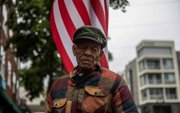 A resident of Tulsa tells people about the history of the area as he stands under a US national flag, before the arrival of US President Joe Biden, in the Greenwood district on the 100th anniversary of the Tulsa Massacre on June 1, 2021