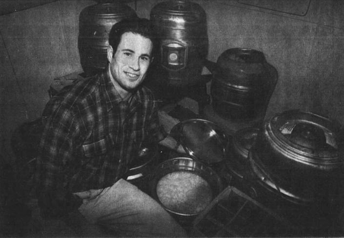 Sam Calagione takes the lid off a keg of Boothbay Barleywine beer that's almost finished fermenting, as seen in a February 28, 1996 clipping from The Daily Times.