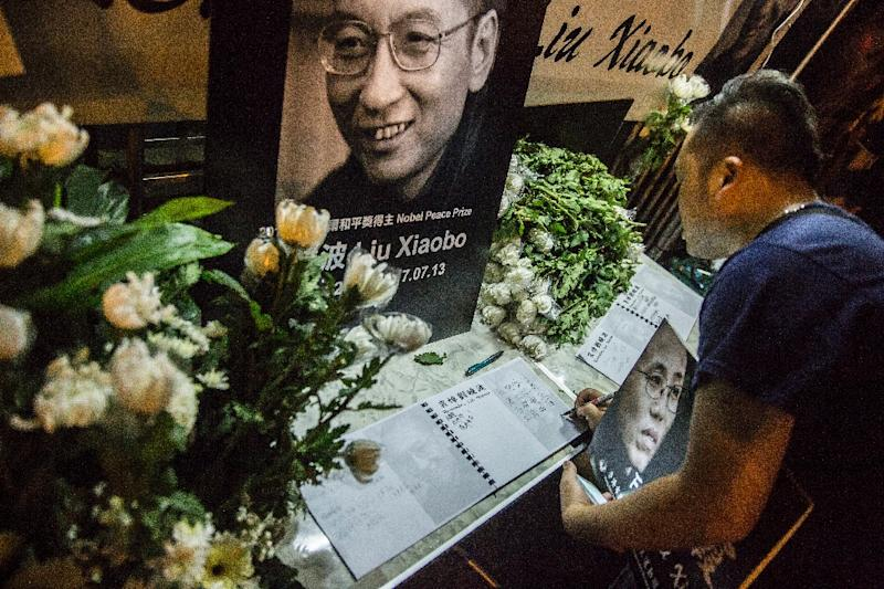 A man writes a message and holds a portrait outside the Chinese Liaison Office of Hong Kong after the death of Chinese Nobel laureate Liu Xiaobo, in Hong Kong on July 13, 2017