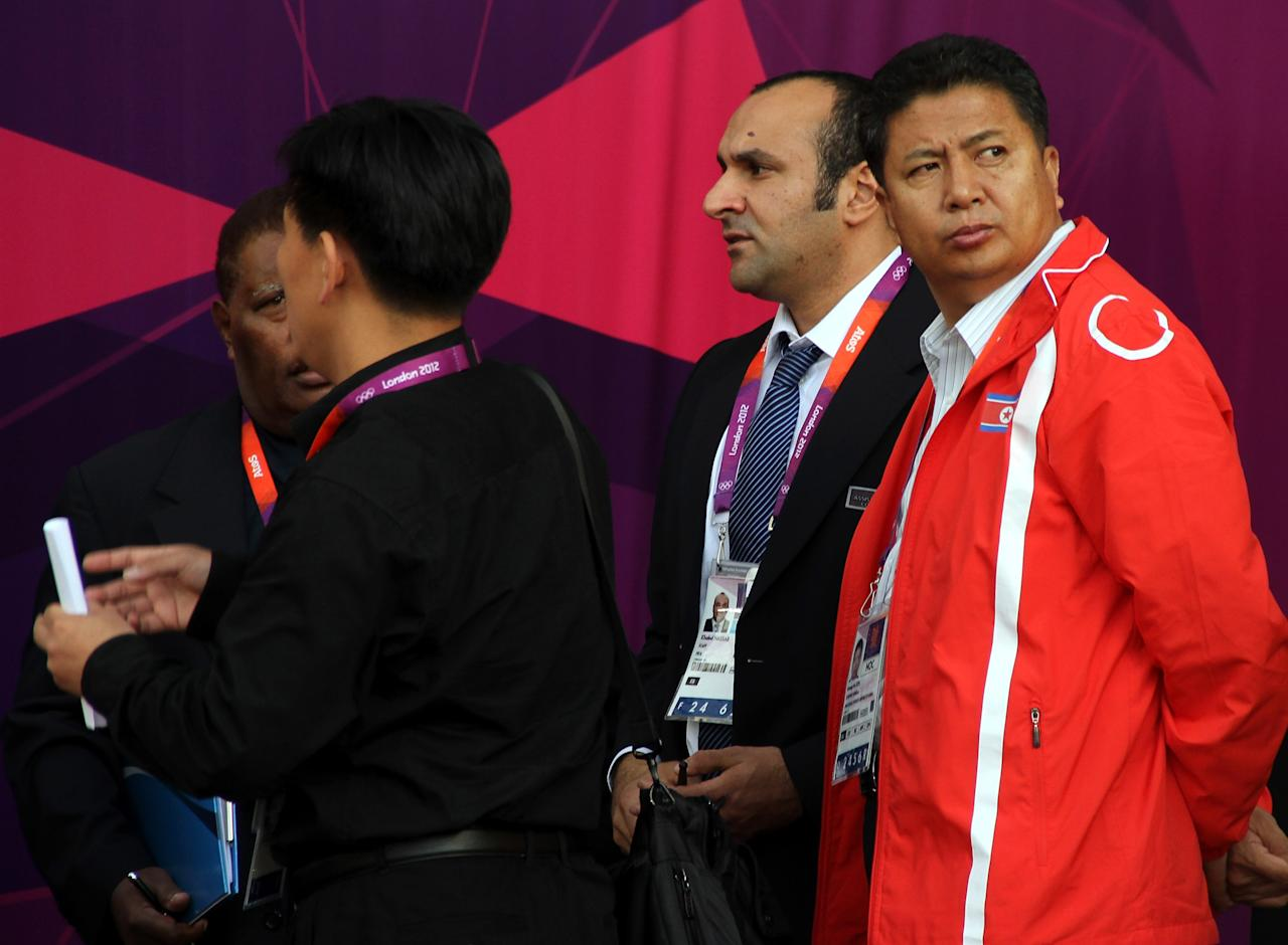 GLASGOW, SCOTLAND - JULY 25:  A DPR Korea official (red jacket) looks on in protest of their national flag wrongly displayed on the scoreboard during the Women's Football first round Group G Match of the London 2012 Olympic Games between Colombia and Korea DPR, at Hampden Park on July 25, 2012 in Glasgow, Scotland.  (Photo by Stanley Chou/Getty Images)