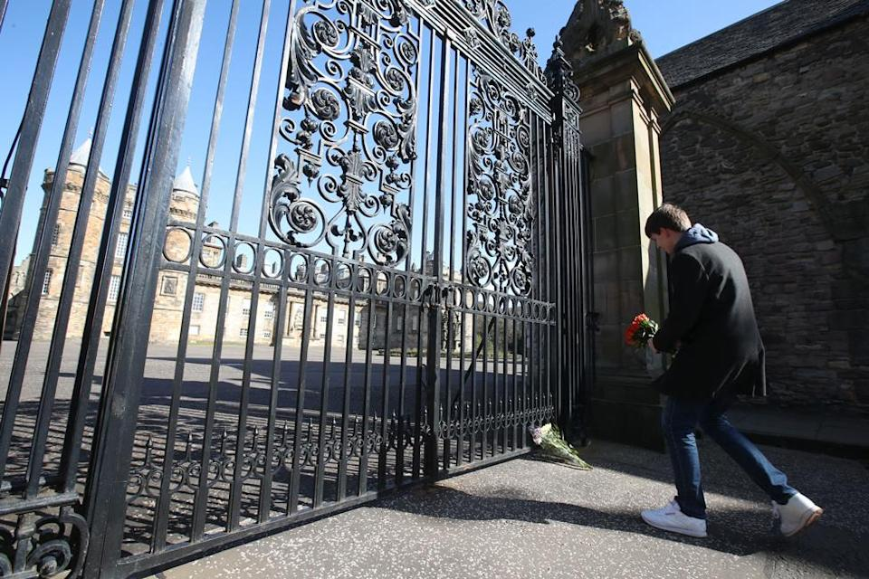 A well-wisher lays a floral tribute at the gates of The Palace of Holyroodhouse in Edinburgh, Scotland