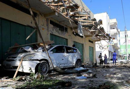 A damaged car is seen at the scene of the afternoon blast near Al Kowsar supermarket in the capital Mogadishu