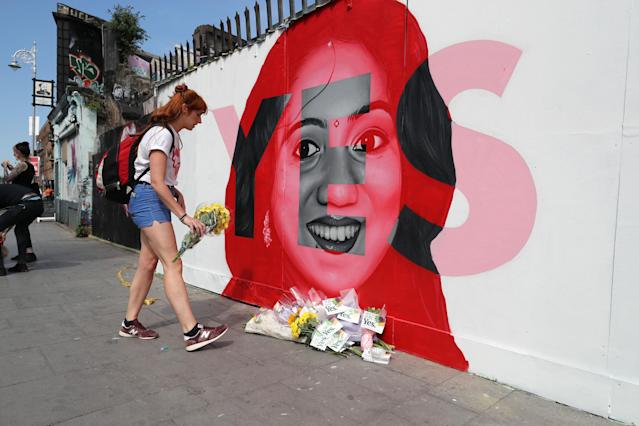 A woman lays flowers next to a mural showing Savita Halappanavar in Dublin, as Ireland goes to the polls to vote in the referendum on the Eighth Amendment of the Irish Constitution. (Photo: Niall Carson/PA Wire)